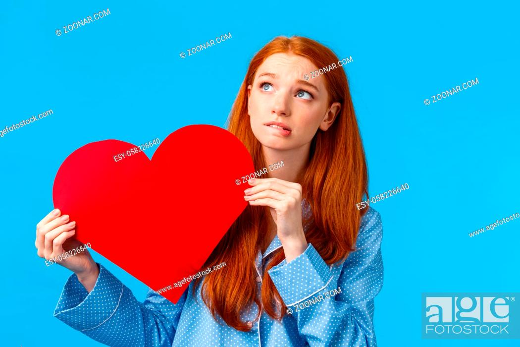 Stock Photo: Shy and indecisive cute girl scared confess love, tell how she feels. Worried cute redhead teenager holding romantic heart card want tell person shes likes her.