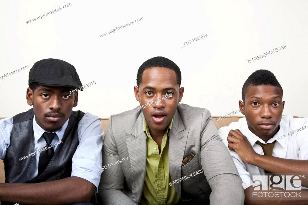 Stock Photo: Three men sitting side by side looking surprised.