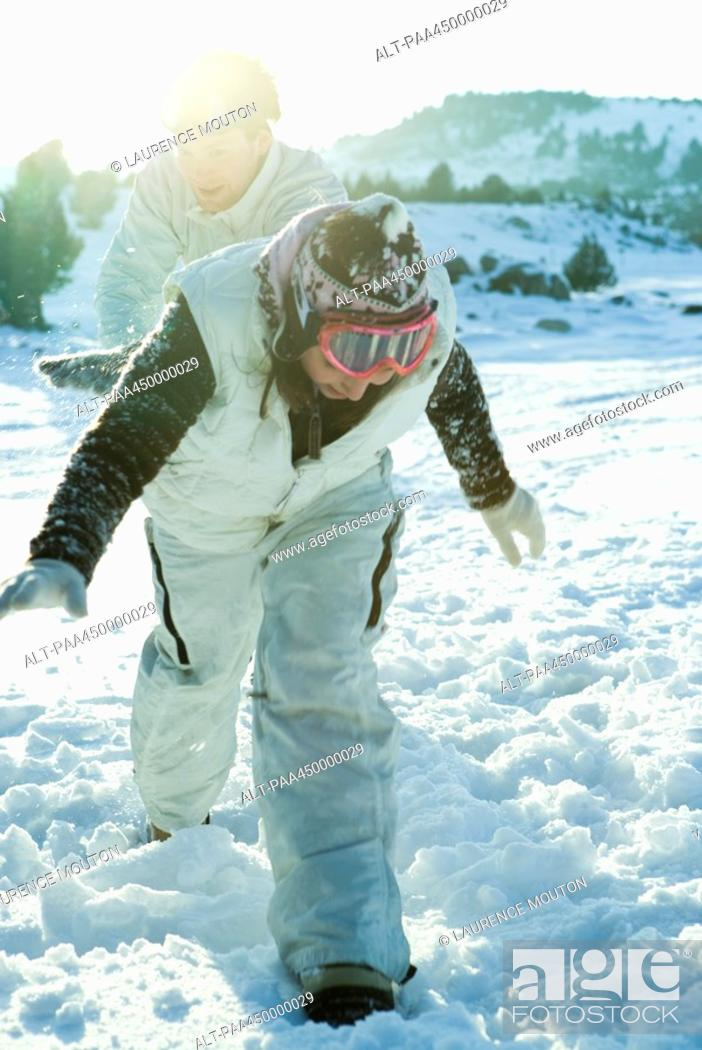 Stock Photo: Teenage girl running in snow, bending over, brother following in background.