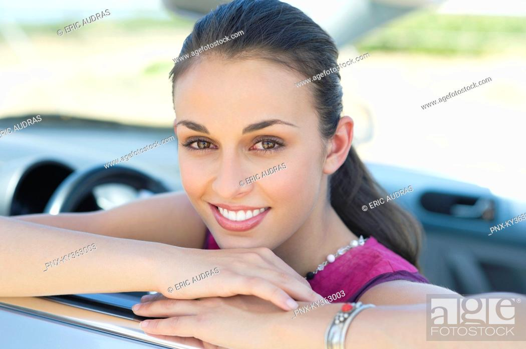 Stock Photo: Young woman leaning on car window.