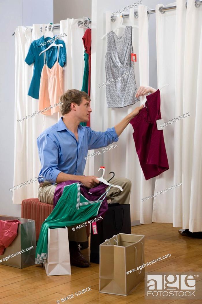 Stock Photo: A man handing a woman clothes.