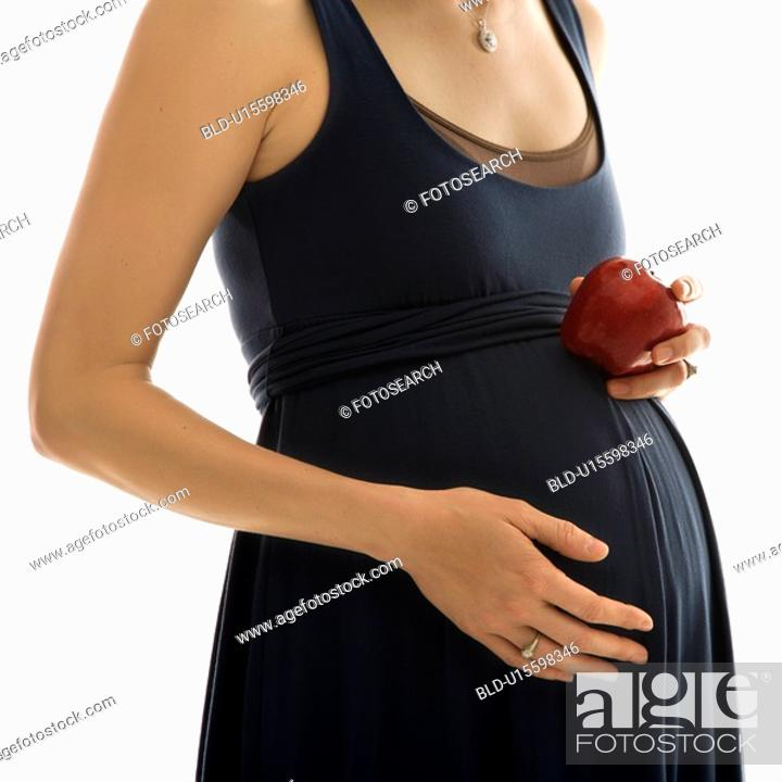 Stock Photo: Portrait of Caucasion mid-adult pregnant woman with hands on belly holding an apple.