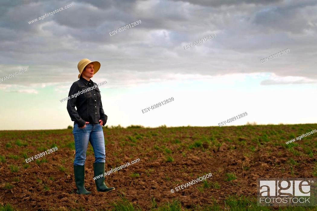 Stock Photo: Portrait of Adult Female Farmer Standing on Fertile Agricultural Farm Land Soil,Looking into Distance.