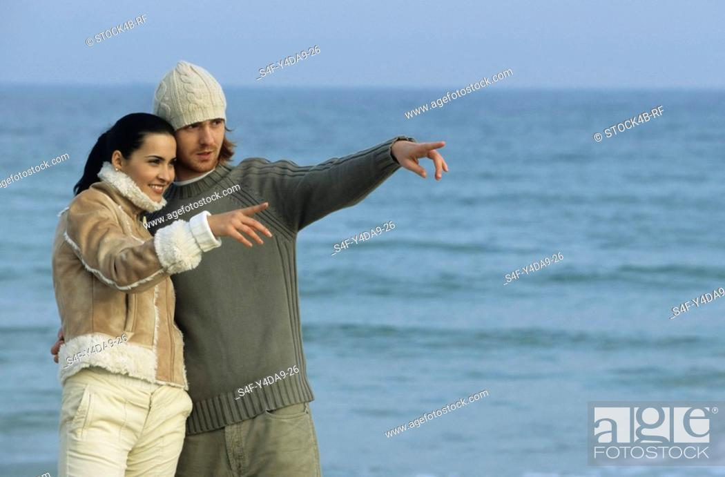 Stock Photo: Couple at the beach pointing at something.