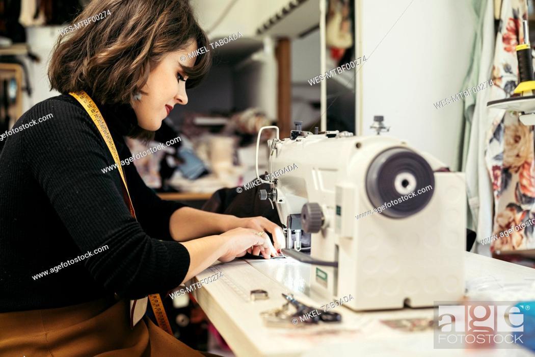 Stock Photo: Young fashion designer using sewing machine.