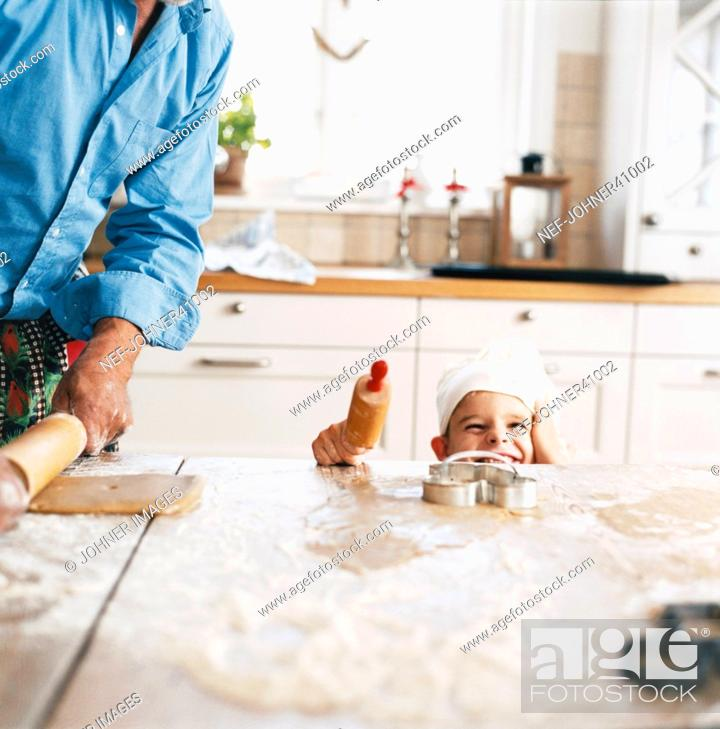 Stock Photo: Smiling boy baking with his father.