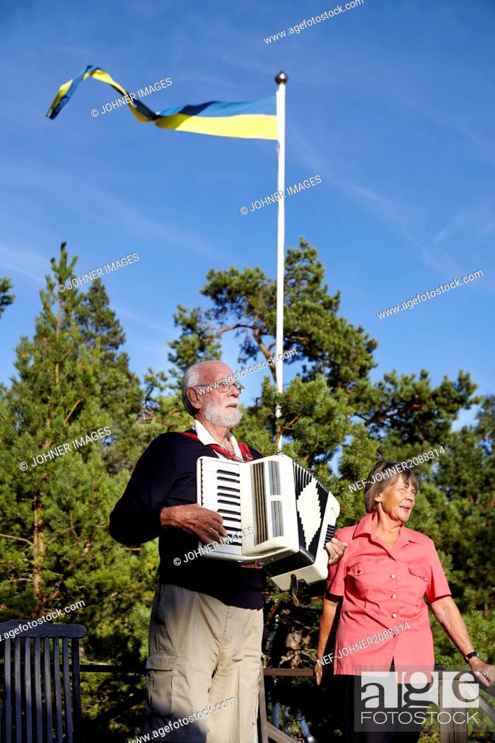 Imagen: Senior man playing accordion to senior woman.
