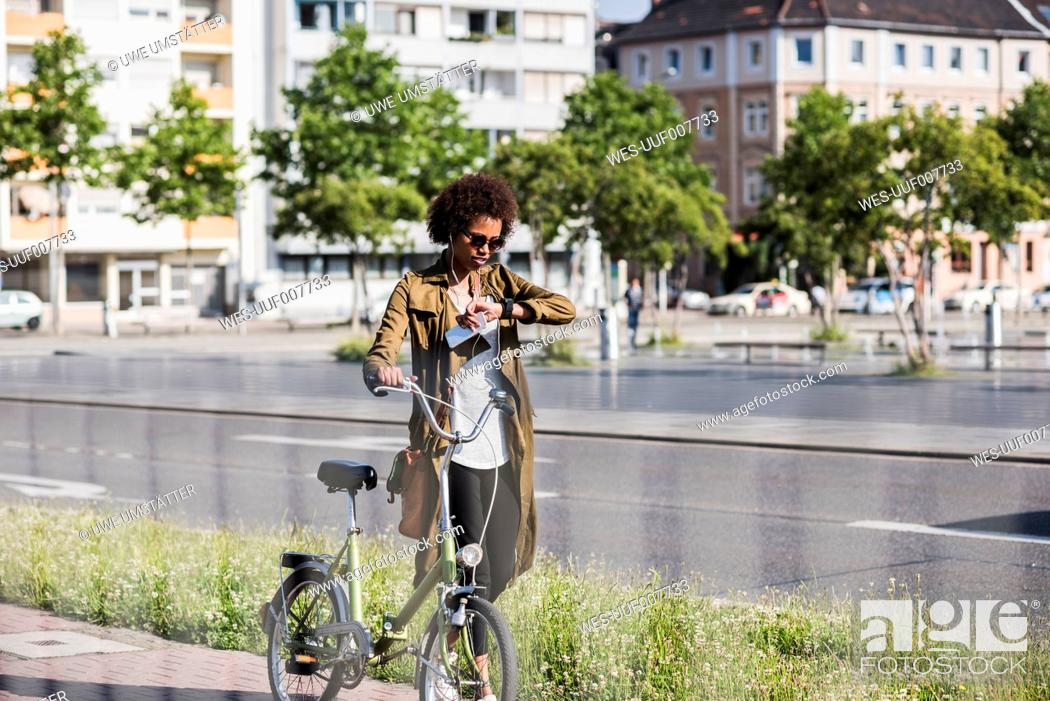 Photo de stock: Young woman with with bicycle checking the time.