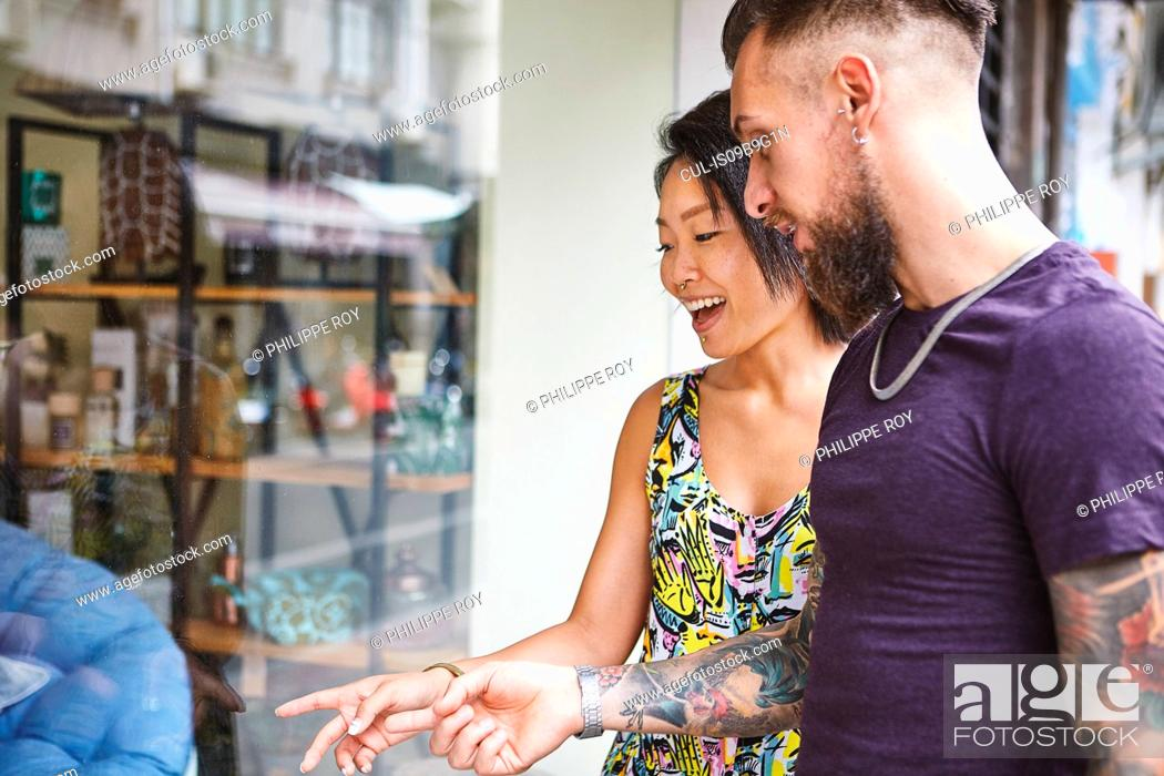 Photo de stock: Multi ethnic hipster couple looking and pointing at shop window, Shanghai French Concession, Shanghai, China.
