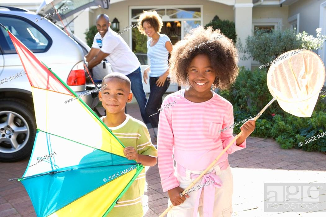Stock Photo: Girl 8-10 with fishing net by brother 6-8 with kite in driveway, smiling, portrait.