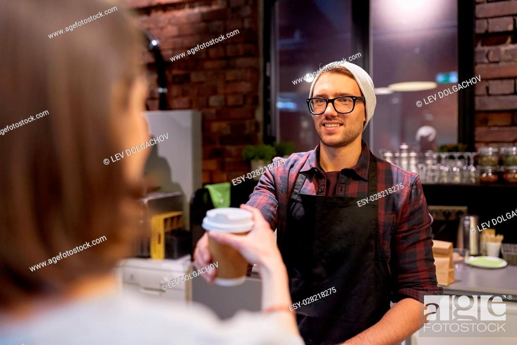 Stock Photo: small business, people and service concept - seller giving coffee cup to woman customer at vegan cafe.