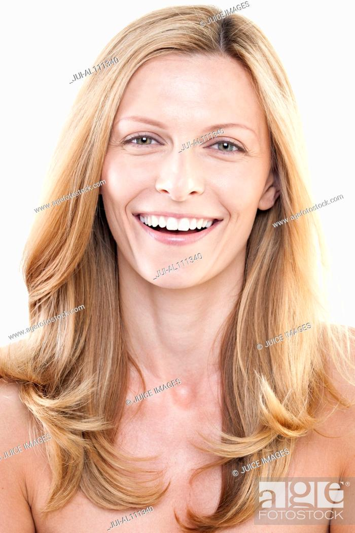 Stock Photo: Portrait of mid adult woman smiling against white background.