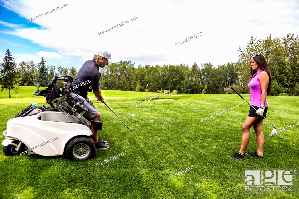 Stock Photo: A physically disabled golfer, using a specialized wheelchair, hits the golf ball with his golf club on the golf green as a female golfer stands watching;.