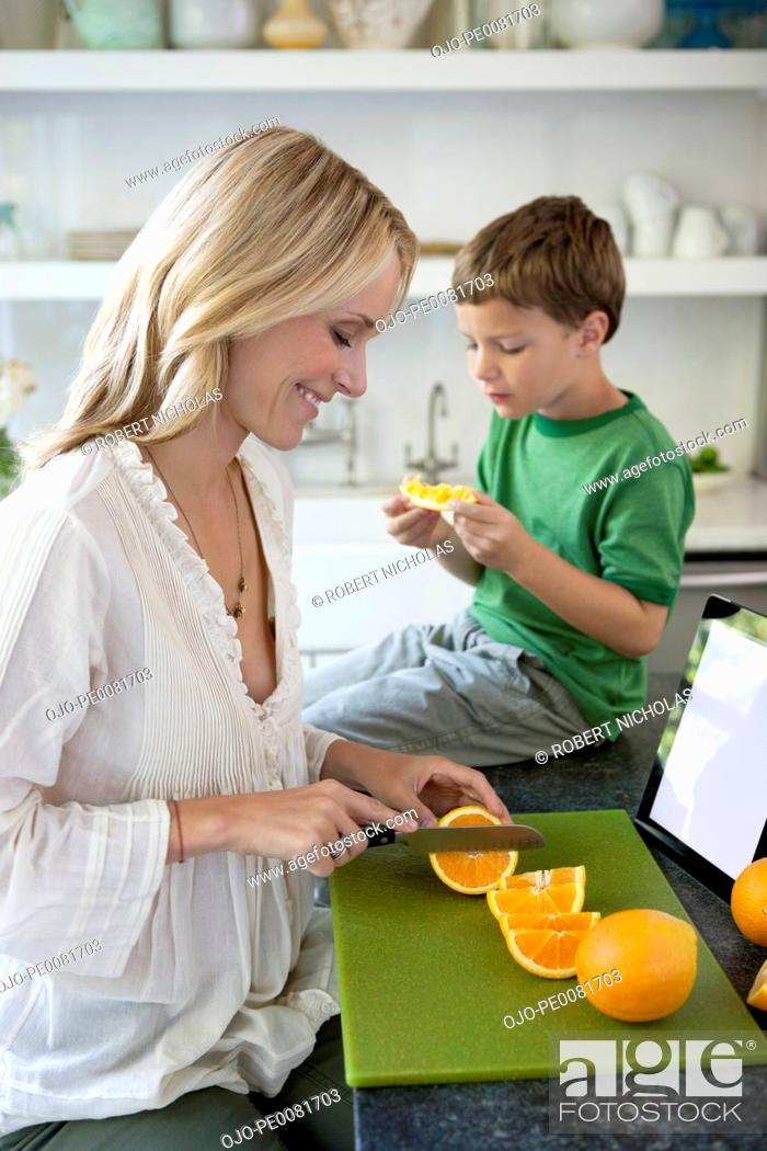 Stock Photo: Mother slicing oranges for son.