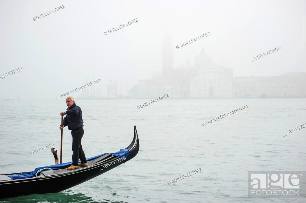 Stock Photo: A Gondola passing by in front of San Giorgio Maggiore In Venice covered in thick fog, Italy.