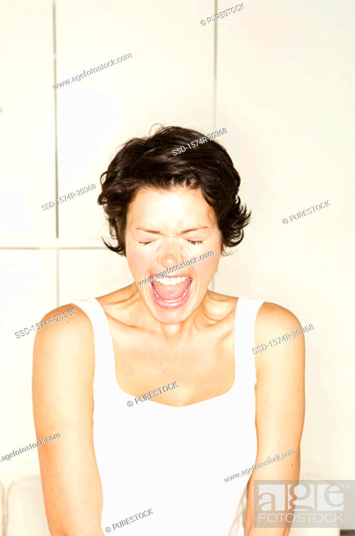 Stock Photo: Close-up of a young woman shouting with her eyes closed.