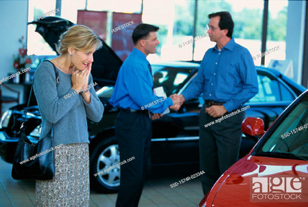 Stock Photo: Mid adult woman looking at a car in a car showroom.