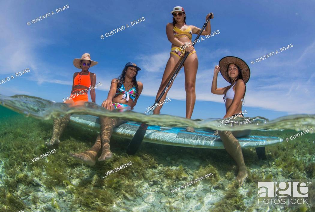 Stock Photo: Four Beautiful Girls With Paddle Board enjoying travel and Vacation on Caribbean beach with turquoise water sea. Fifty fifty Photography.