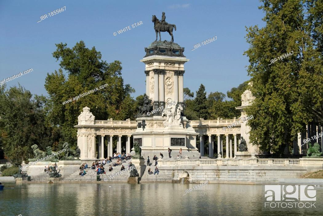 Imagen: View over an artificial lake towards people in front of a monument with an equestrian statue of King Alfosno XII, Parque del Buen Retiro.