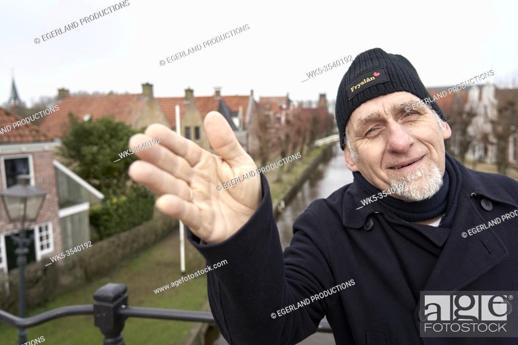 Stock Photo: senior man leading the way in Sloten, Friesland, Netherlands.
