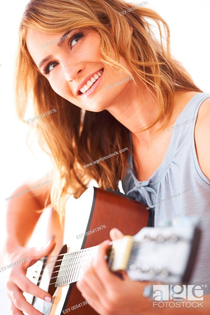 Stock Photo: Smiling young woman holding her guitar and playing some music.