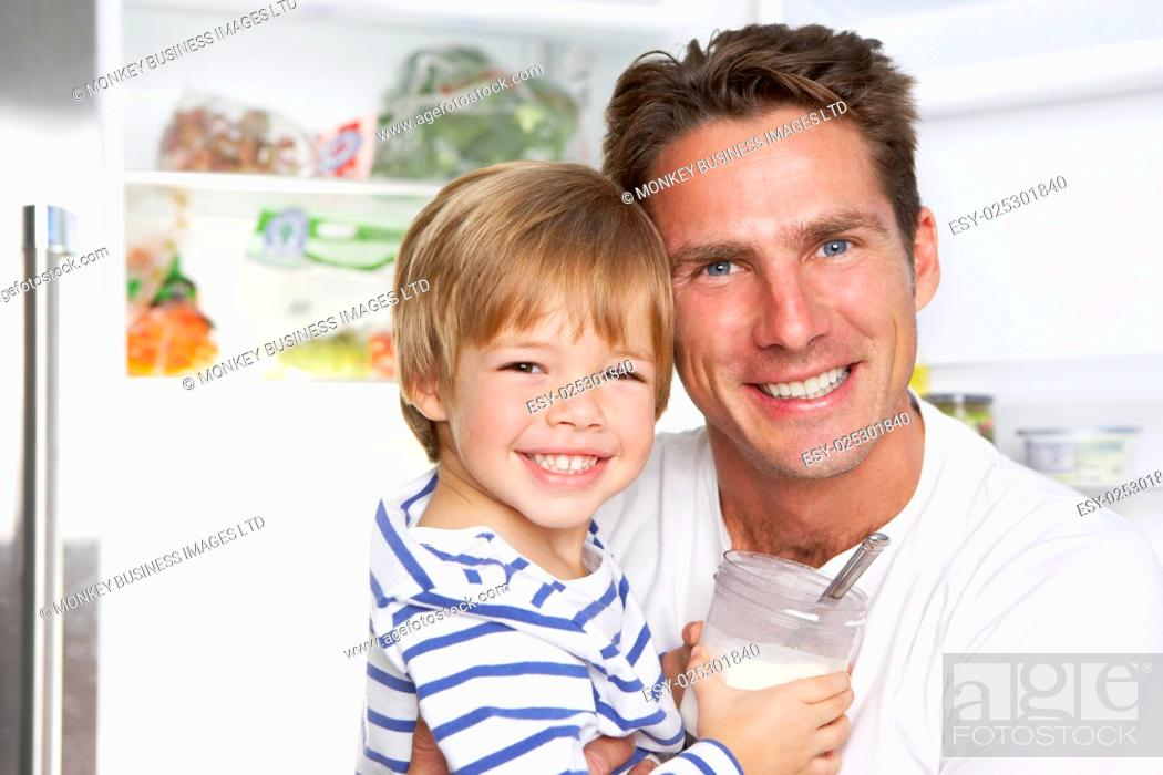 Stock Photo: Father And Son Getting Snack From The Fridge.