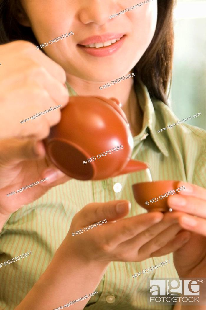 Stock Photo: Close-up of a person's hands pouring tea into a cup held by a young woman.