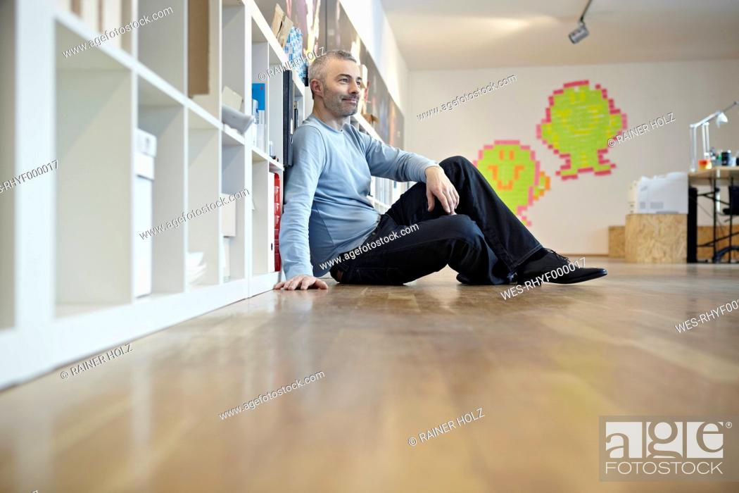 Stock Photo: Germany, Cologne, Mature man sitting on floor.