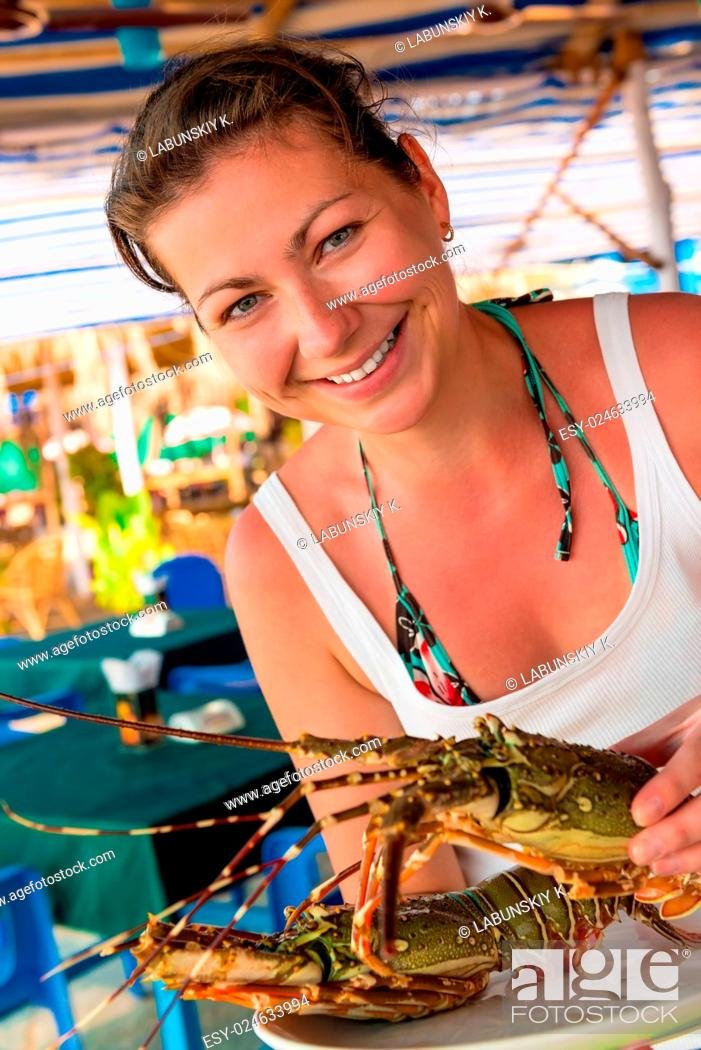 Stock Photo: girl holding a raw lobster and smiling.