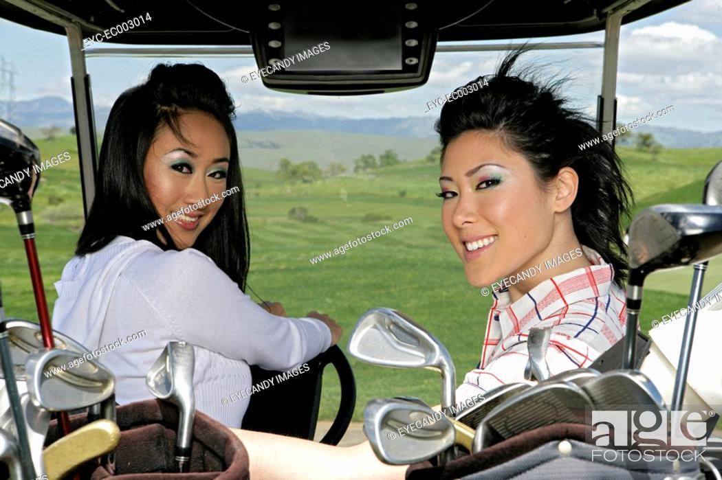 Stock Photo: Portrait of two women sitting inside a golf cart.
