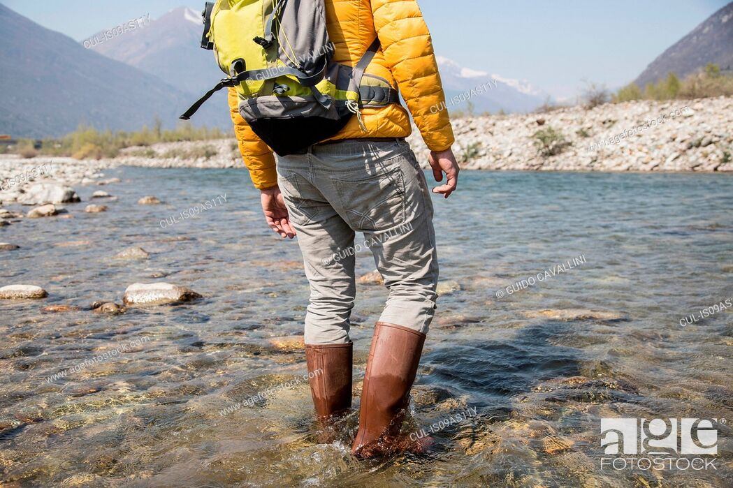 Imagen: Cropped rear view of young male hiker crossing Toce river, Vogogna, Verbania, Piemonte, Italy.