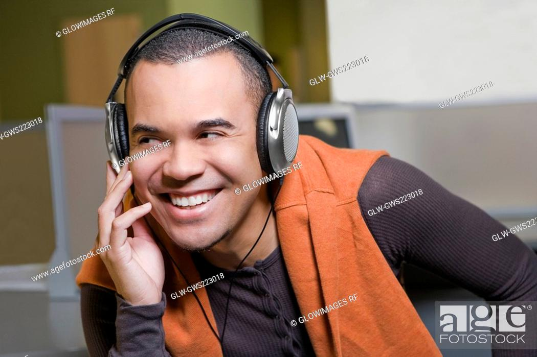 Stock Photo: Close-up of a young man listening to music and smiling.