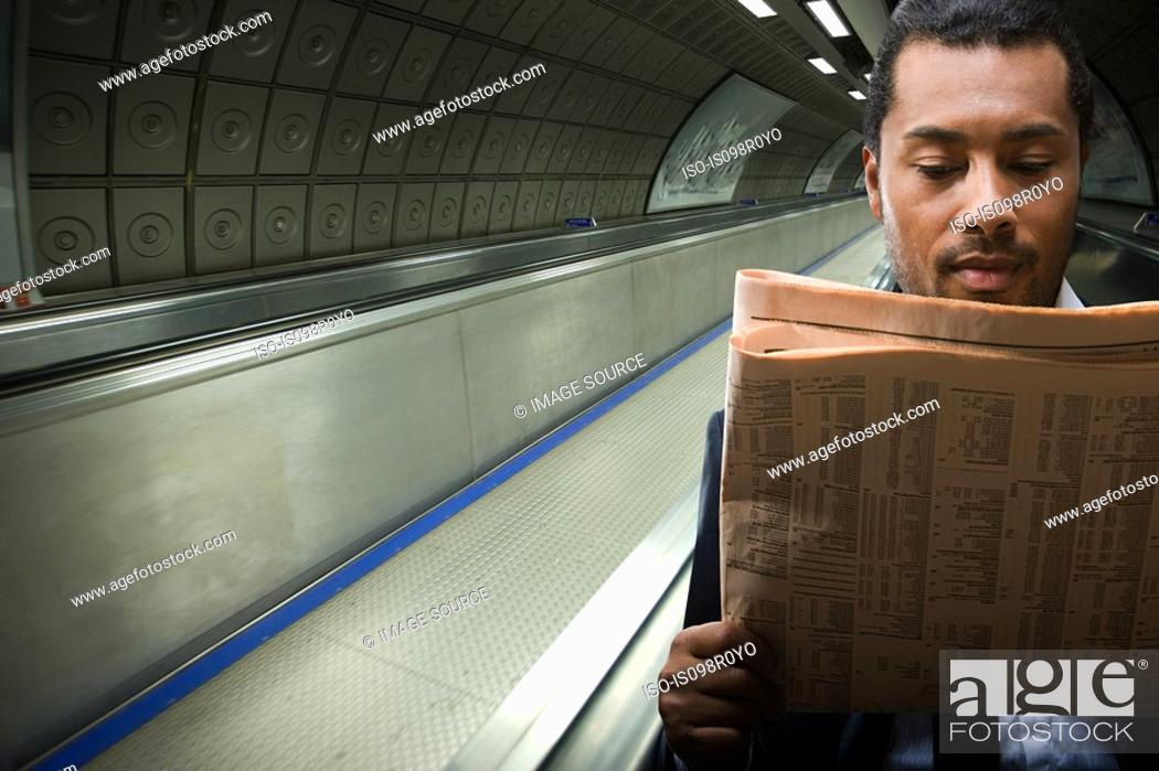 Stock Photo: A businessman reading a newspaper.
