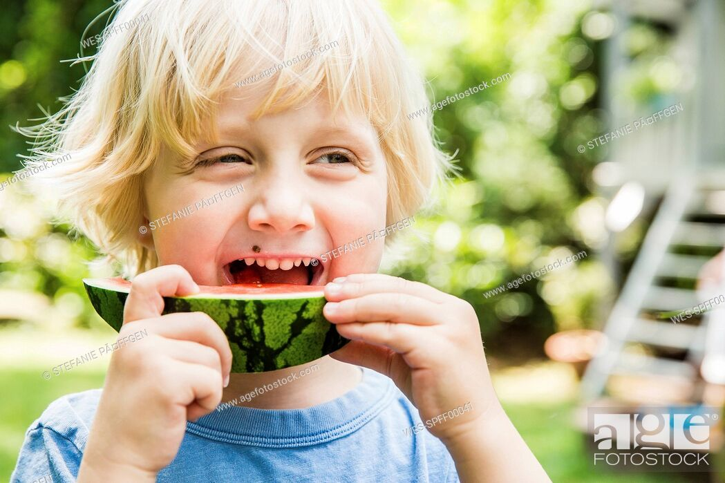 Stock Photo: Portrait of little boy eating slice of watermelon.