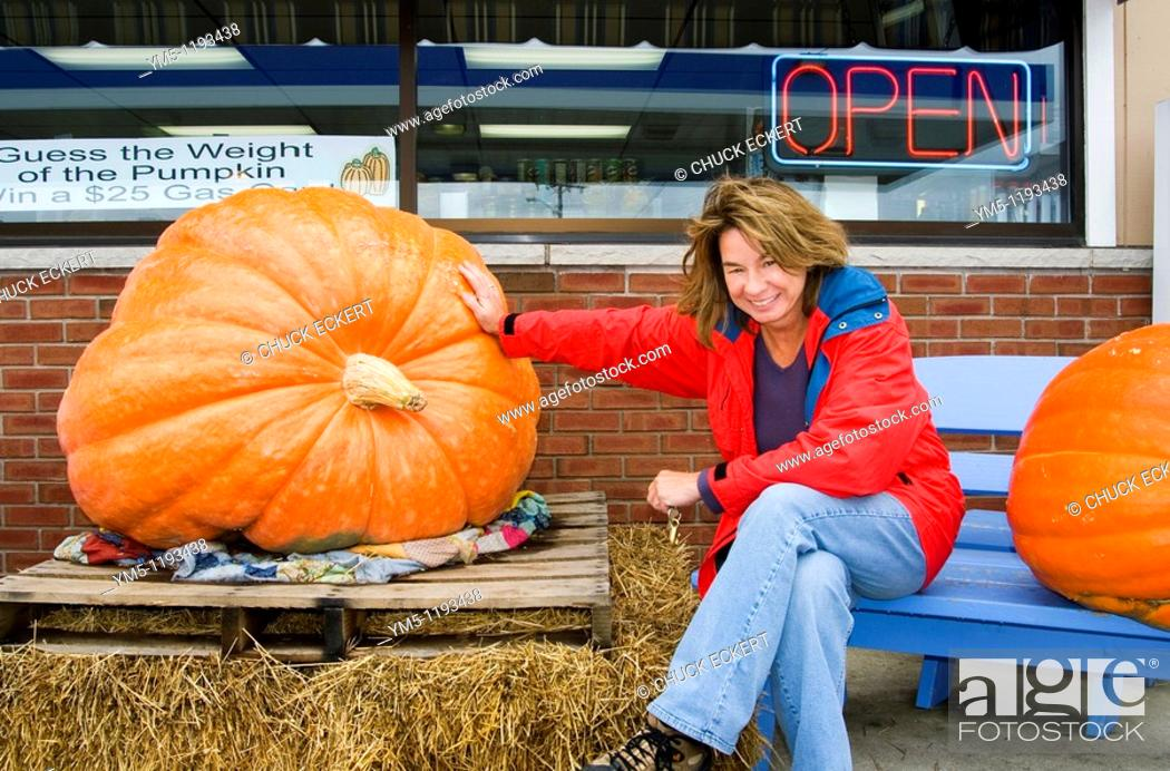 Stock Photo: Susan Zavodny of Barrington, IL next to a huge pumpkin at a gas station in Sister Bay, Wisconsin  If you guess the exact weight of the pumpkin you win $25 00.