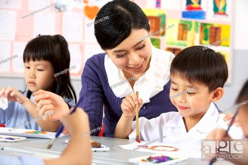 Stock Photo: Teacher Helping Students During Art Class In Chinese School Classroom.