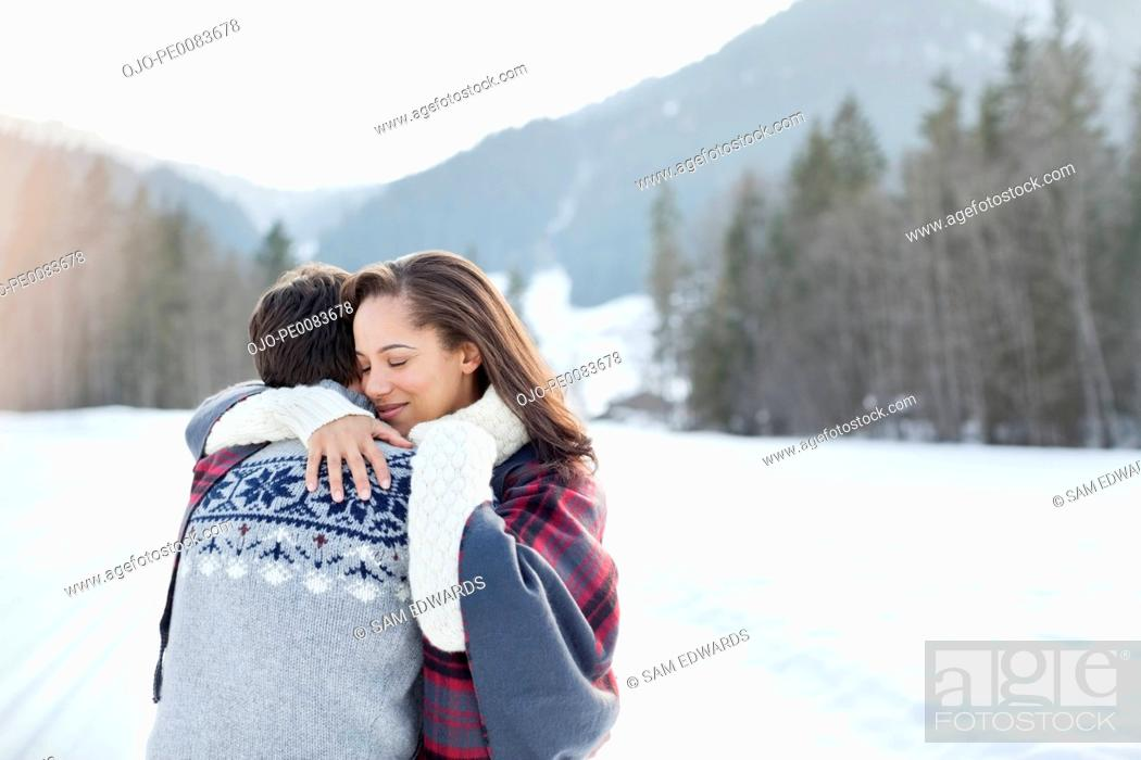 Stock Photo: Smiling woman hugging man in snowy field.
