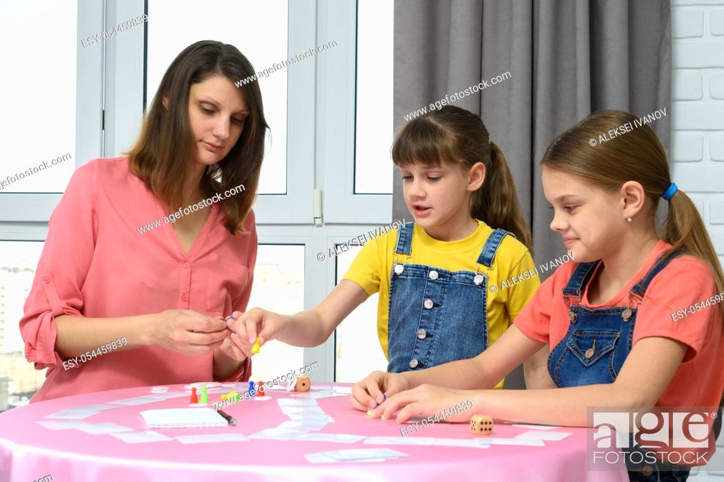 Stock Photo: Mom and two daughters play board games at home on vacation.