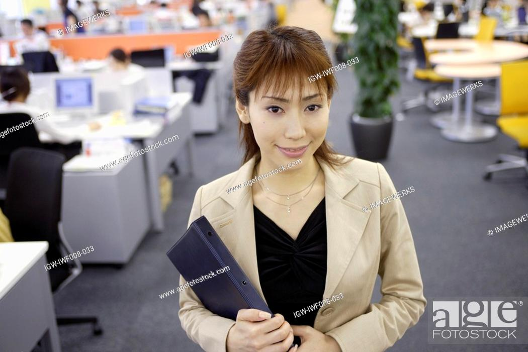 Stock Photo: A woman holding a diary smiles at the camera.