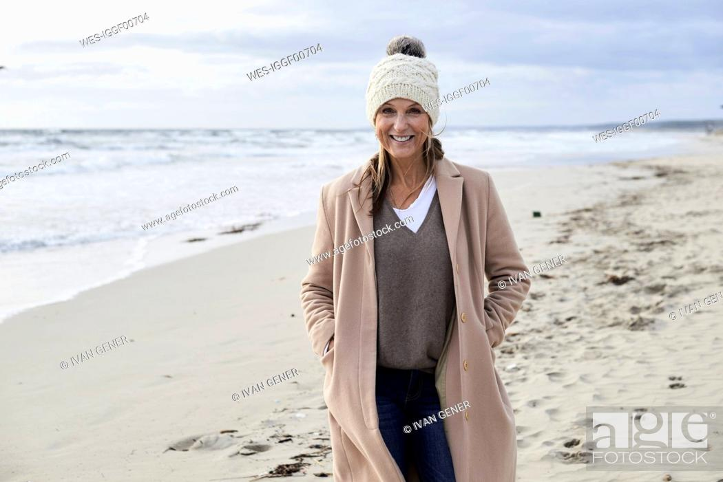 Photo de stock: Spain, Menorca, portrait of smiling senior woman wearing bobble hat and coat on the beach in winter.