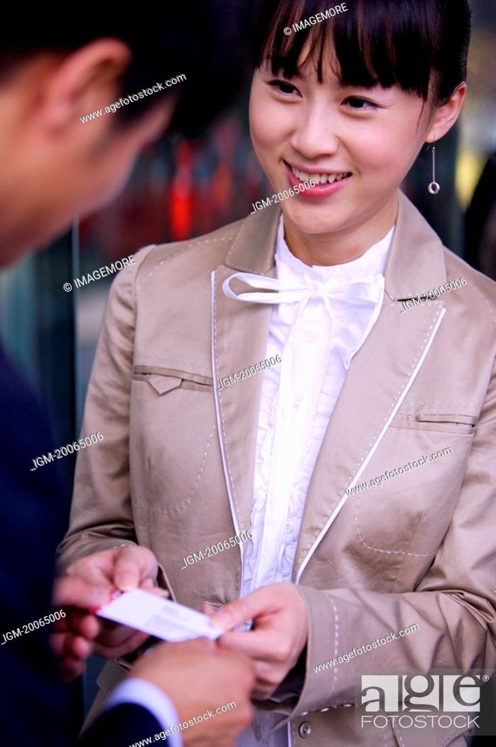 Stock Photo: Young woman delivering name card to young man and smiling.