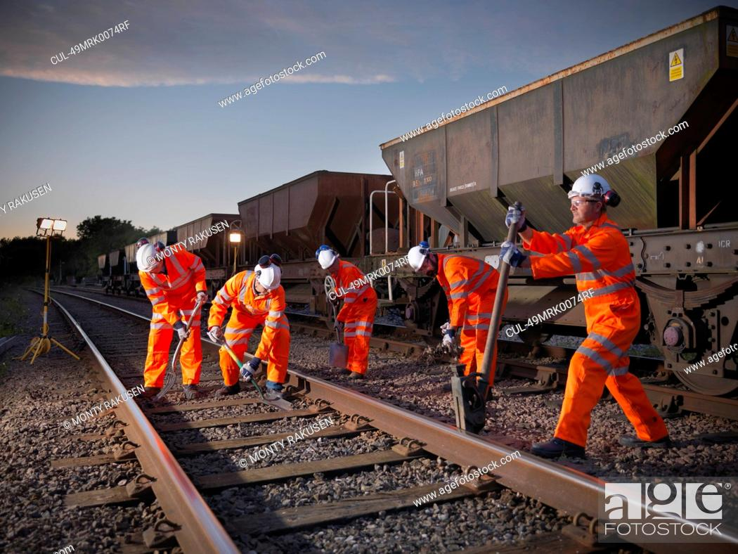 Stock Photo: Railway workers adjusting train tracks.
