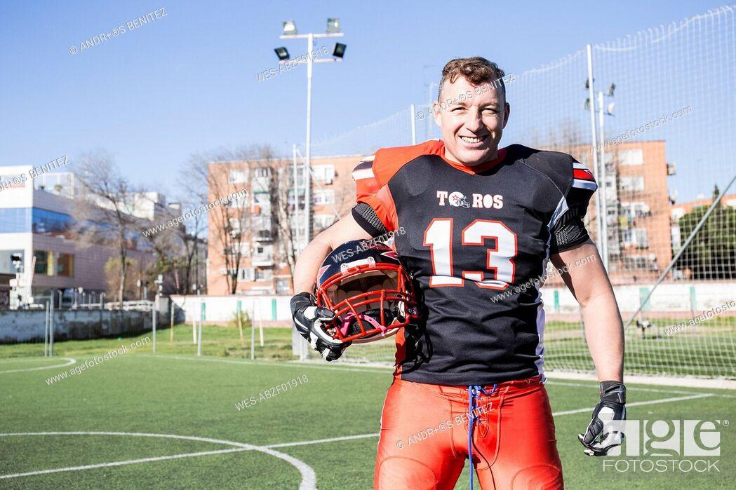 Stock Photo: Portrait of smiling American football player holding helmet.
