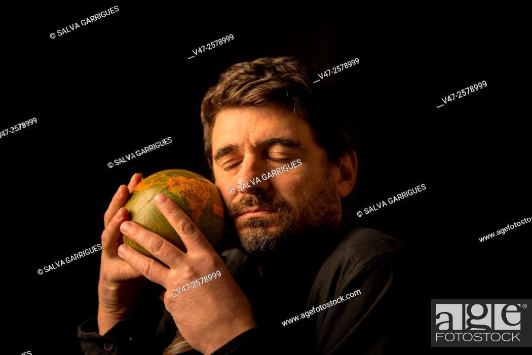 Imagen: Man embracing the globe with the eye closed, black studio photo sobrefondo.