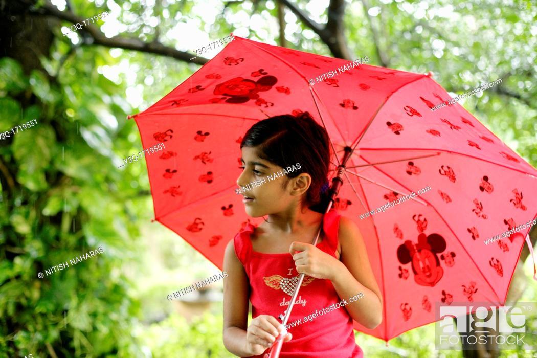 Stock Photo: Innocent young girl holding an umbrella and enjoying the monsoon rains.