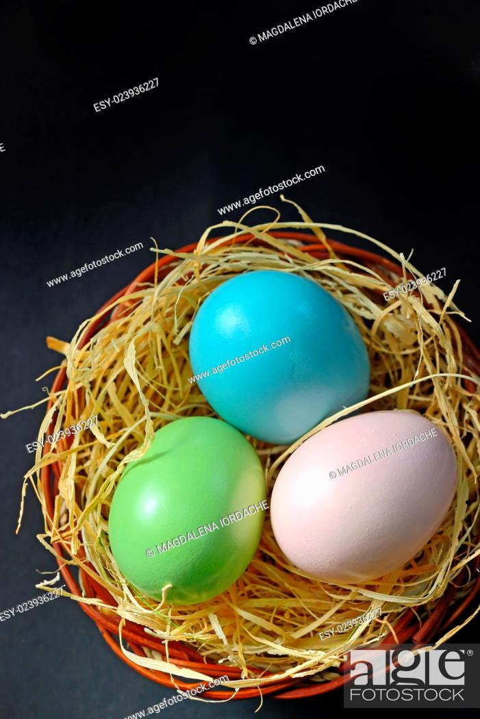 Stock Photo: Easter eggs in the nest on black background.