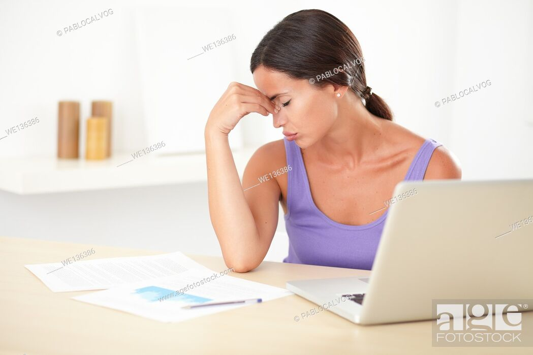 Stock Photo: Pretty woman with a headache working on the computer while sitting at her home.