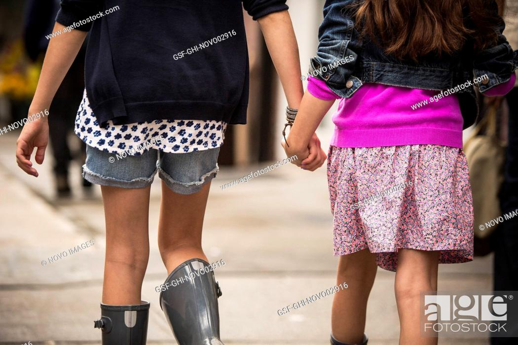 Imagen: Two Young Girls Holding Hands While Walking Down Sidewalk, Close-Up Rear View.
