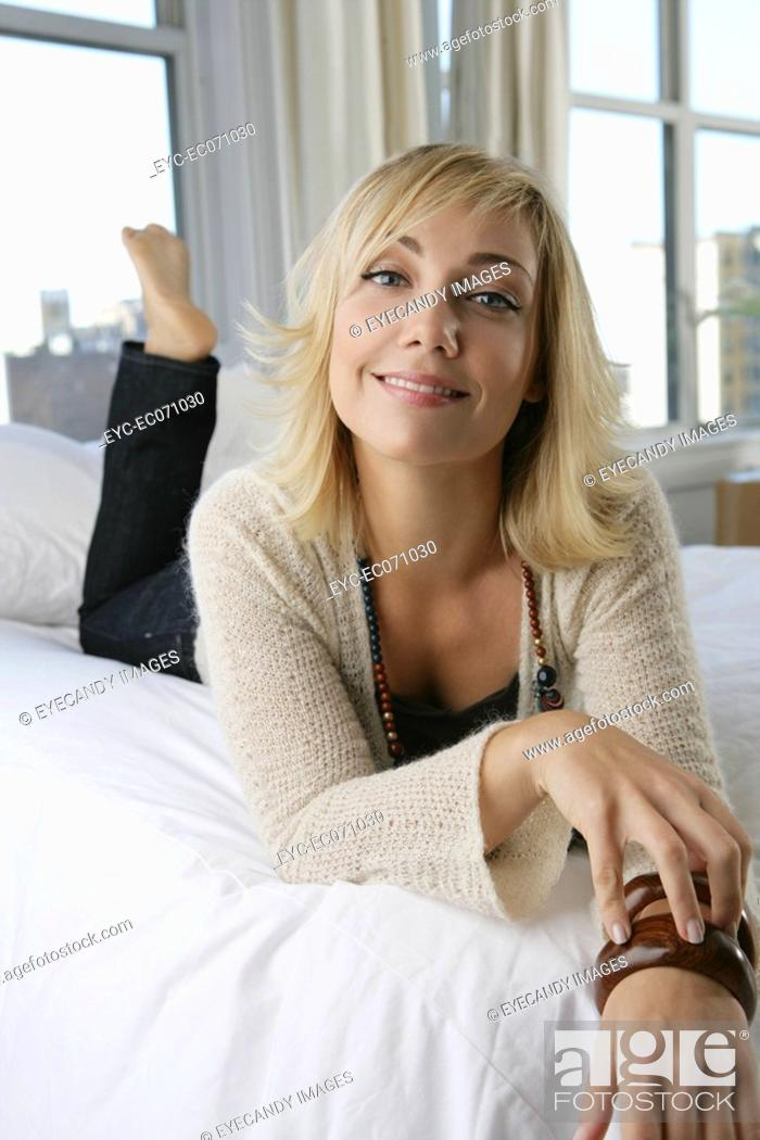 Stock Photo: Young happy woman relaxing in bed.