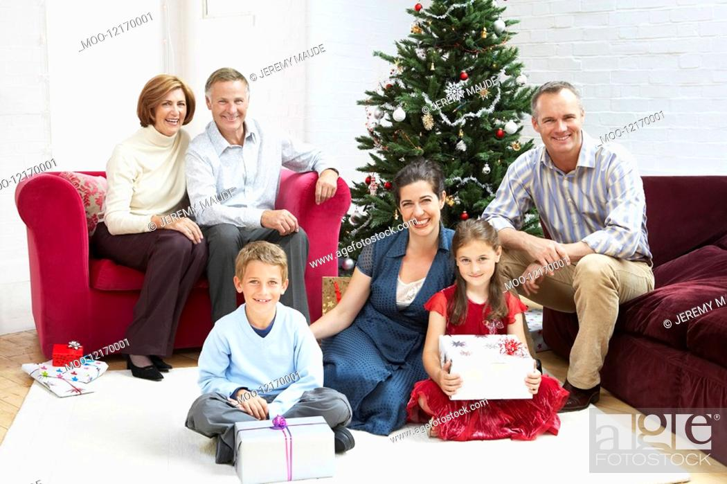Stock Photo: Family sitting by christmas tree in living room portrait.